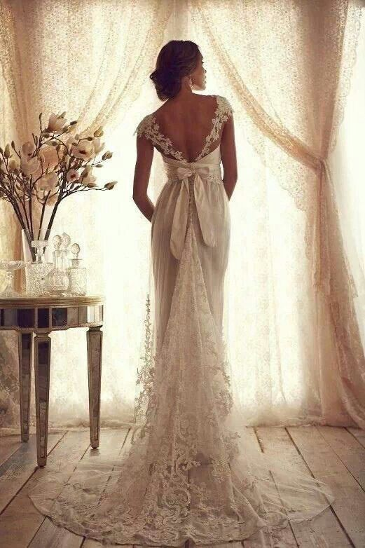 Old fashioned wedding dress, lace, bows, and cap sleeves at an off the shoulder style