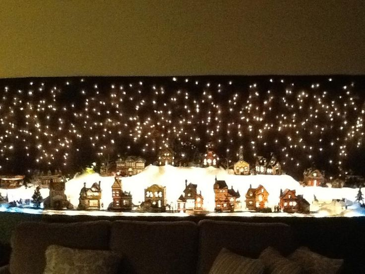 My Christmas village Backdrop is icicle lights hung on the wall with black fabric over them.