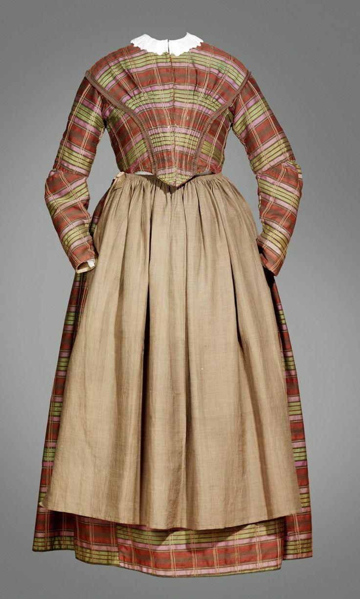 """Meeste vrouwen in West-Friesland kleedden zich halverwege de 19de eeuw volgens de mode. Ze droegen geen korset, maar """"rompie"""", een getailleerd lijfje zonder mouwen. In plaats van hoepelrok droegen ze een aantal onderrokken over elkaar, zodat ze hetzelfde effect bereikten. Typisch waren de zogenaamde hangende kappen. Bij dit hoofddeksel hoorde nog een aantal sieraden, zoals oorijzer en voorhoofdsnaald. De hier getoonde japon is gebruikt als bruidsjurk rond 1860-1880. #NoordHolland…"""