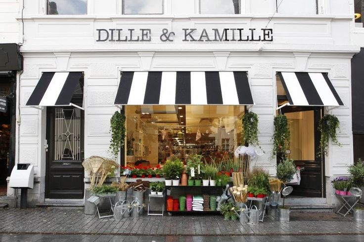 Love the simplicity of this shop - the white walls, the black all caps lettering and the black and white awnings.