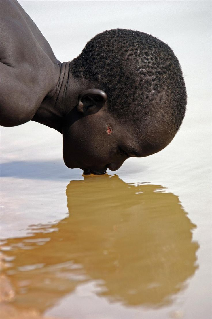 In December 2005 in southern Sudan, a boy drinks water from the Akuem River, near the village of Malual Kon in Bahr el Ghazal State. Only about one-third of the population has access to safe drinking water, and the threat of water-borne disease has increased as towns swell due to the return of displaced people and refugees following decades of civil war.    2005 © UNICEF/NYHQ2005-1987/Georgina Cranston    http://www.unicef.org