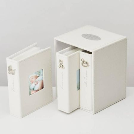 This is a lovely set of three keepsake photo albums for a new born gift, Christening , Baptism, or Naming day.   The albums are presented in a matching case all are covered with an ivory linen fabric Each album is for a special time in Baby's early months.  Album 1 is Newborn, the 2nd album is for First Events, the 3rd for As I Grow, with silver lettering and a silver decoration along the spine.   There is a frame on the front cover of each album for a 2.5x2.5 inch photo and 18 plastic sl...