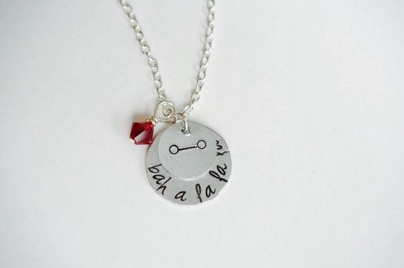 Disneys Big Hero 6 inspired necklace featuring the words from the fist bump Hero and Baymax share, Bah- a- la la la. Its accented with a Baymax