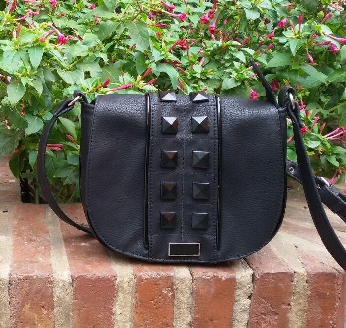 Material: 100% PU.  Detalles:   Apertura frontal por boton iman.  Interior forrado.  Manija larga regulable.  Argollas, hebillas y tachones al tono.  Color: Negro.