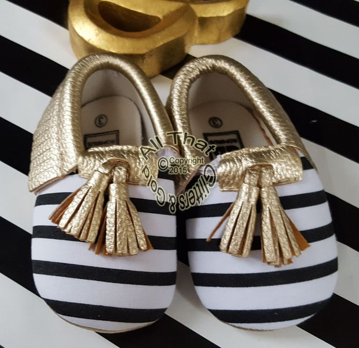 Gold, Black and White Striped Soft Soled Baby Girl Moccasin Shoes With Tassels Sizes 0 to 24 monthsLet these soft soled gold, black and white striped slipper feet walk all over you! These soft soled baby girl moccasin shoes are so comfortable and stylish. These are designed with cute tassels and made with an elastic band so it will be easy to slip your little ones feet into. What Your Order Includes:1 Pair of Shoes----------------------------------------------------------------