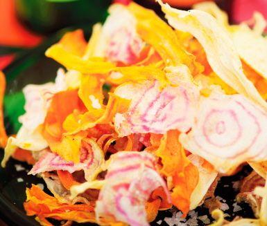 Ett nyttigt och färggrant alternativ till chips får du genom dessa färgglada chips, gjorda på morötter, rödbetor och palsternacka. Enkelt att torka på en plåt i ugnen, och en given succé för både vuxna och barn.