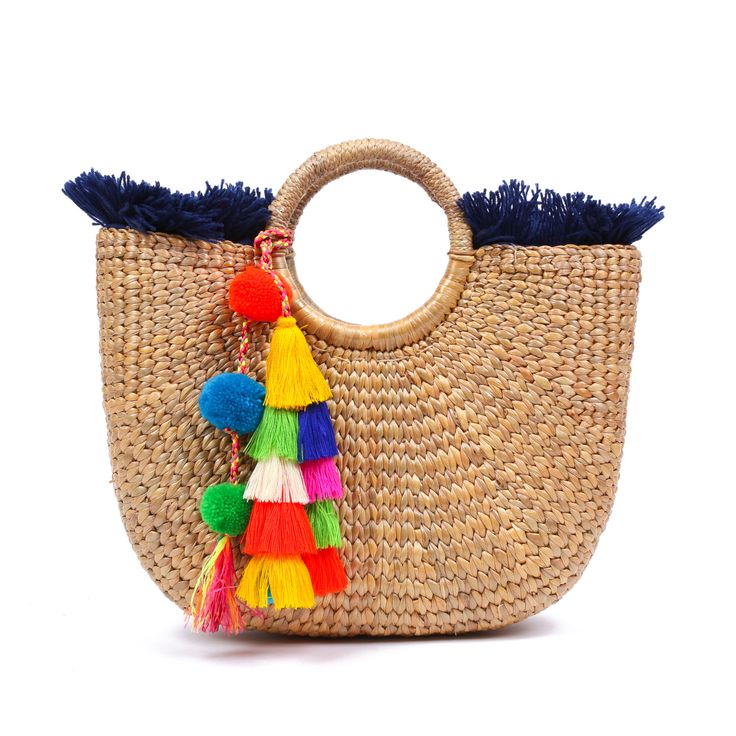 Handwoven hyacinth basked lined with multicolored textile and decorated with a tassel pom pom charm. Dimensions: 12 x 9 x 4 inches