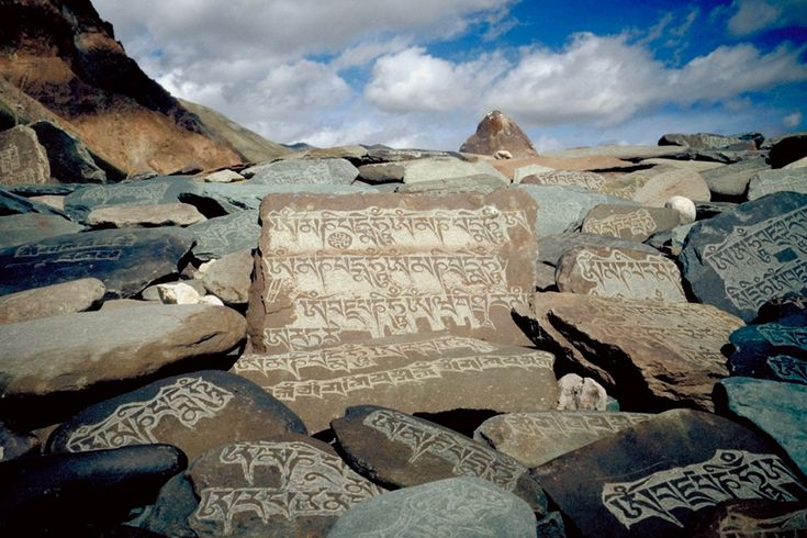 """Along the paths of Zanskar in the state of Jammu & Kashmir, India, the traveller is often confronted with Mani-Walls. These stone structures are a compilation of exquisitely-carved stone-tablets, each with the inscription """"Om Mani Padme Hum"""" which translates to """"Hail to the Jewel in the Lotus"""". These walls should be passed or circumvented from the left side, the clockwise direction in which the earth and the universe revolve, according to Buddhist doctrine."""