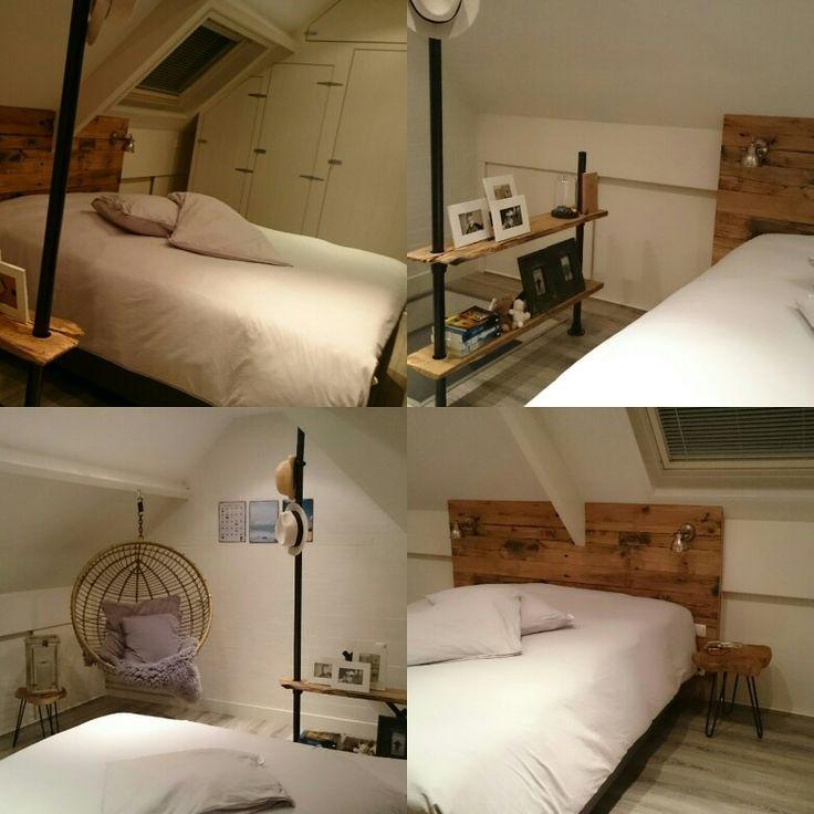 Zolder slaapkamer met eikenwagondelen en zwarte stijgerbuizen.