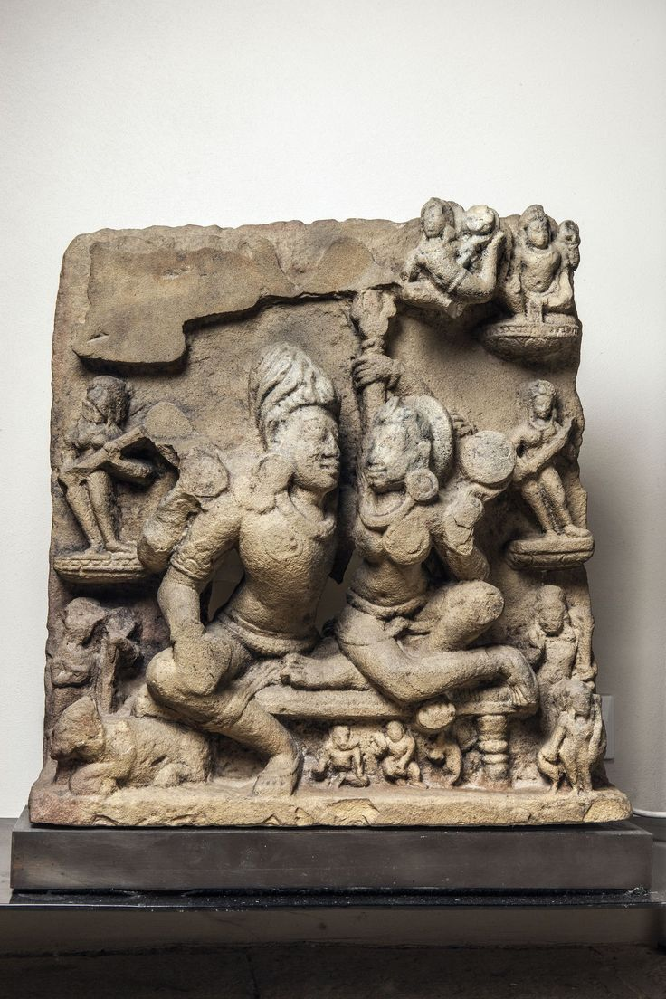 Umamahesvara illustrant Shiva et Parvati tendrement enlacés, la Shakti du dieu de l'amour sur ses genoux, Shiva tenant le trisula coiffé du haut chignon d'ascète et entouré du panthéon shivaïte sur trois registres : Apsaras, Gandharvas, divers divinités et attendants et à ses pieds son fidèle serviteur et véhicule le taureau Nandi Pierre grès beige. Inde centrale. Période Post Gupta. 7 ème à 9 ème siècle. Ht 83 x 56cm. Cassures et manques.