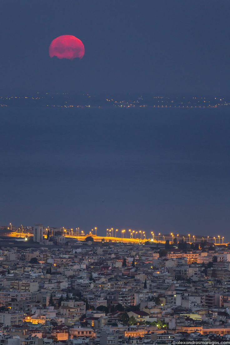 """The Waxing Gibbous Moon (98.8%) sets over the Harbour of Patras, Greece's third largest urban area on Wednesday, July 1st, 2015 a few hours after the country missed the deadline for a $1.8 billion debt payment to the IMF. Greece's last-minute overtures to international creditors for financial aid on Tuesday were not enough to save the country from becoming the first developed economy to default on a loan with the International Monetary Fund (IMF). - Getty Images: <a href=""""..."""