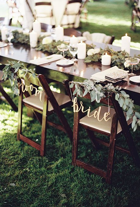 Chairs with eucalyptus and wildflower garlands and signs from @bhldn   Brides.com