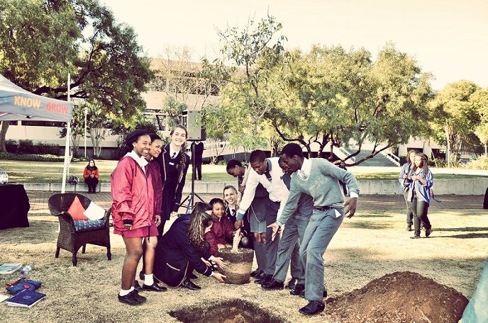 Children from two different schools in Bloemfontein plant a tree together at the University of the Free State.