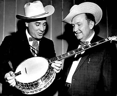 Earl Scruggs holds his brand new $900 Earl Scruggs model banjo while his partner, Lester Flatt, looks on. Scruggs designed the banjo, which the Vegas Company would produce. by Jimmy Ellis (The Tennessean - 1960)