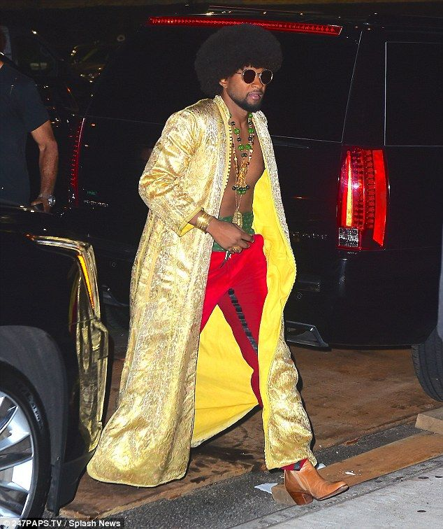 Cool dude: Usher looked seriously slick in an open gold coat, worn with red…