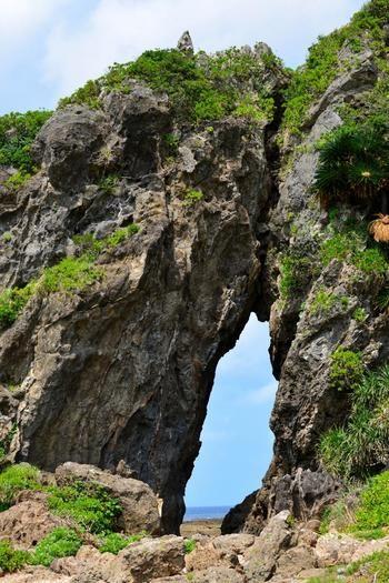 """久米島には大きな穴が特徴的な「ミーフガー」と呼ばれる岩があり別名""""女岩""""とも言われていて、400万年以上前に出来たとされています。手前の広場までは車で行けますが、そこから先は歩いて向かいます。"""