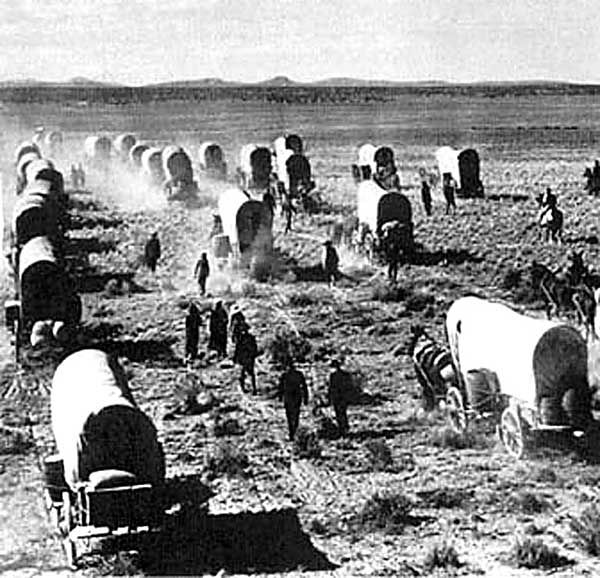 """Mormon Pioneers crossing the plains. Thomas Bullock, noting the arrival of this company, writes: """"About 5 p.m. Captain Andrus passed the office having banners inscribed, """"Holiness to the Lord"""", on one side of the wagon and on the other side, """"Hail to the Governor of Deseret"""". Thomas Cartwright - My Relatives"""