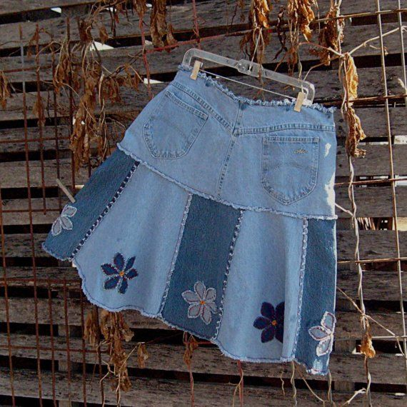 "A reworked knee length jean skirt featuring alternating light and medium tone denim panels. Daisy appliques on each of the 8 flared panels are done in my signature shaggy denim style.    For something just a little bit different, the hem is shaped in scallops.     I removed the original waistband and gave this jeans skirt a new comfy soft frayed waist. This is ""new"" waist has a post button with loop closure and decorative stitching. It is reinforced on the inside with twill tape to hold its…"