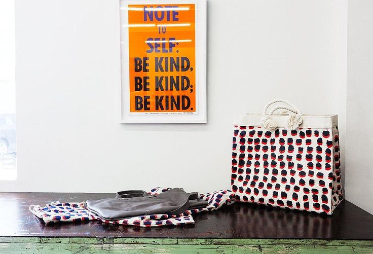 "One motto that everyone in the studio tries to stick to: Be Kind. Here a bright orange framed art print hangs on the wall behind polka dot leather bags. See the full tour and read more from ""Inside the Studio Tour of Inspiring Bag Designer Clare Vivier"" over on the One Kings Lane Style Guide!"