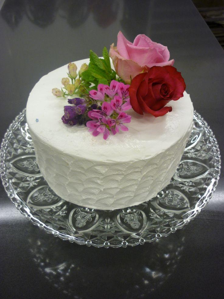 Buitenzijde met merengue/schuim en gedecoreerd met eetbare bloemen.