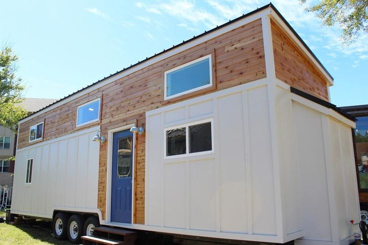 """This gorgeous modern tiny house is the """"Everest"""" by Mustard Seed Tiny Homes. The 34-foot tiny home features a ground floor master bedroom with vaulted ceilings, full size bed, storage drawers under the bed, and a large closet. A sliding glass door provides a great view and easy outdoor access from the bedroom."""