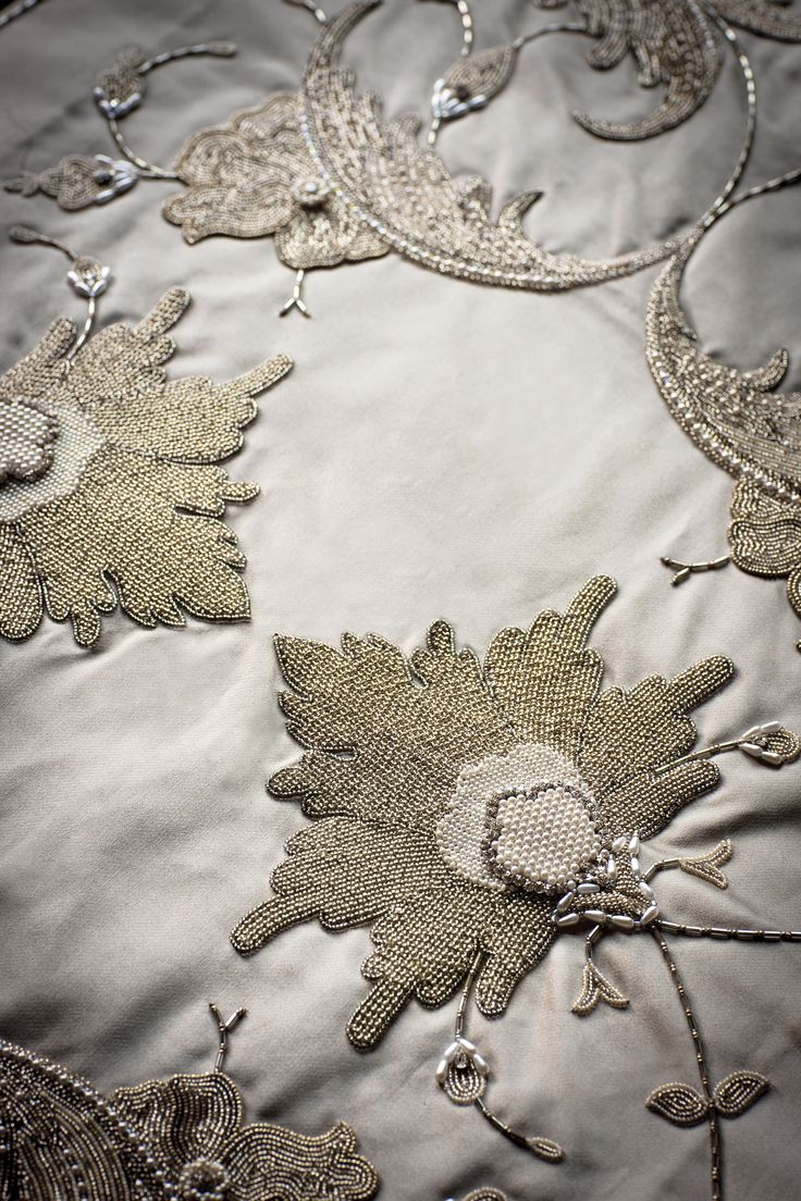 Rigoletto is a wonderfully opulent embroidery. The mirrored abstract pattern of interlocking flowers and leaves is painstakingly covered in thousands of tiny pearls and beads. The exquisite detail found in this couture fabric design is exceptional, and creates a show stopping piece to be proud of.