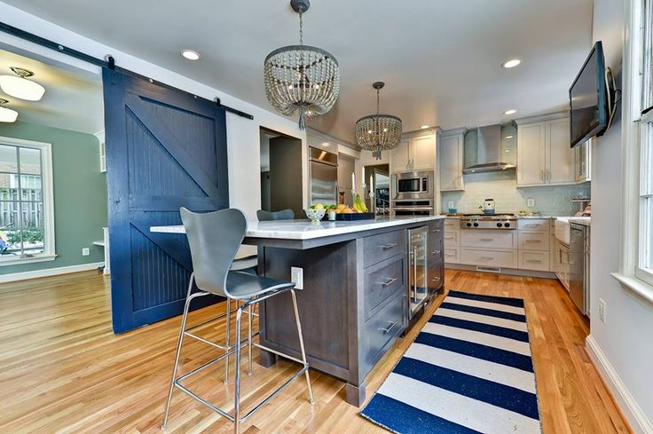 Love the blue sliding barn door and how it matches the blue striped rug. Feels very nautical.