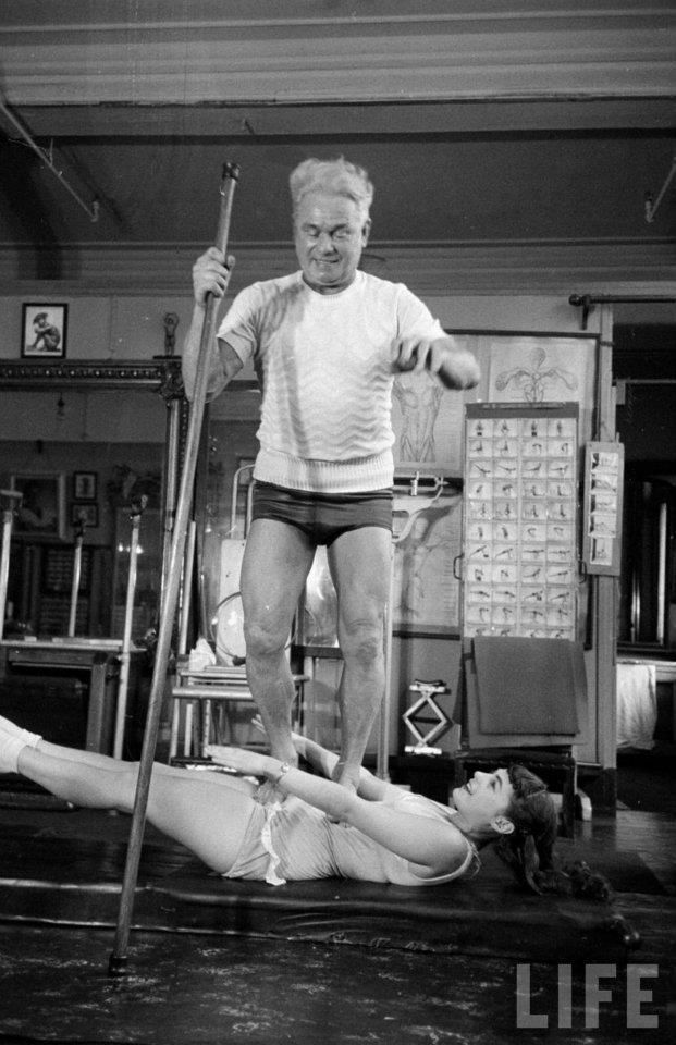 Vintage Joseph Pilates standing on his client doing the 100.
