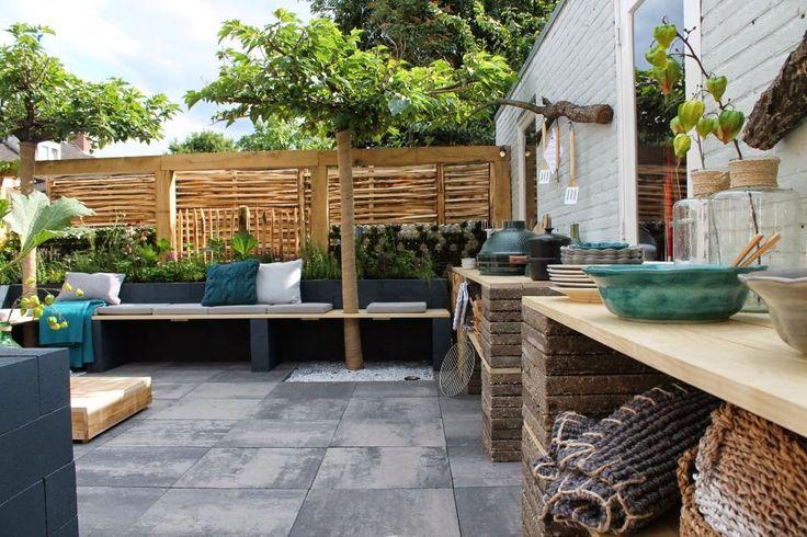 Tuinbank gemaakt van stapelblokken en buitenkeuken van oude tegels en steigerhouten planken, sierbestrating van MBI ; terrastegels Plaza 60x60x6cm Kleur Grijs-Zwart