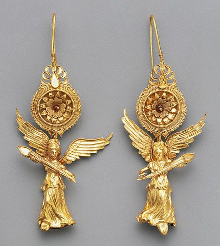 Greek, 225 - 175 B.C.  Gold and glass. Earrings with Nike Pendants (Getty Museum) Flying figures of Nike, the Greek goddess of victory, form the main decoration of these Hellenistic gold earrings. The goddess appears with spread wings and wind-swept drapery, holding a flaming torch, in two figures that are mirror images of one another. Each tiny figure is hollow, made from two joined sheets of gold that were formed in a mold.