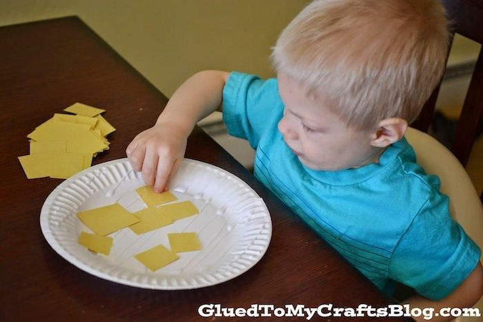 little blond boy, sticking yellow pieces of paper, on white paper plate, easter crafts for preschoolers, easy and fun idea