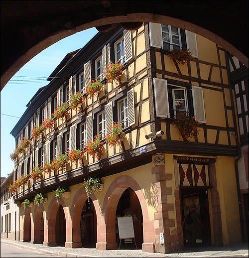 La rue des Bouchers : vous y trouverez, en haute saison, l'office du tourisme situé au rez-de-chaussée d'une très belle maison à arcades, surmontée de deux étages à colombages. En face, belle maison à colombages, avec un porche. Remontez la rue, puis empruntez la rue Neuve.