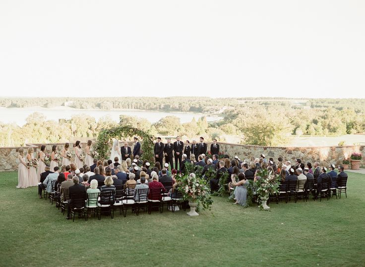 stunning outdoor wedding ceremony at bella collina featured a large, loose and organic arch filled with local greenery, vines and branches. two large garden urns filled with wild greenery and fall flowers marked the entry to the aisle.
