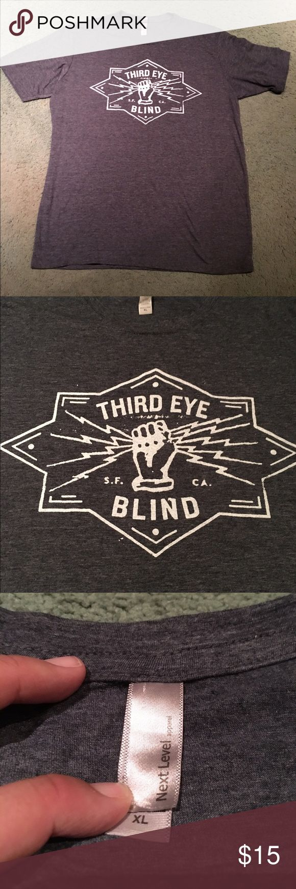 Third Eye Blind T-Shirt * Third Eye Blind t-shirt. T-shirt brand is Next Level Apparel.   * Pre-owned- great condition, no holes or stains.  * Made of 65% polyester & 35% cotton.  * Size XL.  * Measurement: Underarm to underarm flat across is approximately 22 1/2 inches. Back of neck to bottom of hem is approximately 29 inches. Third Eye Blind Tops Tees - Short Sleeve