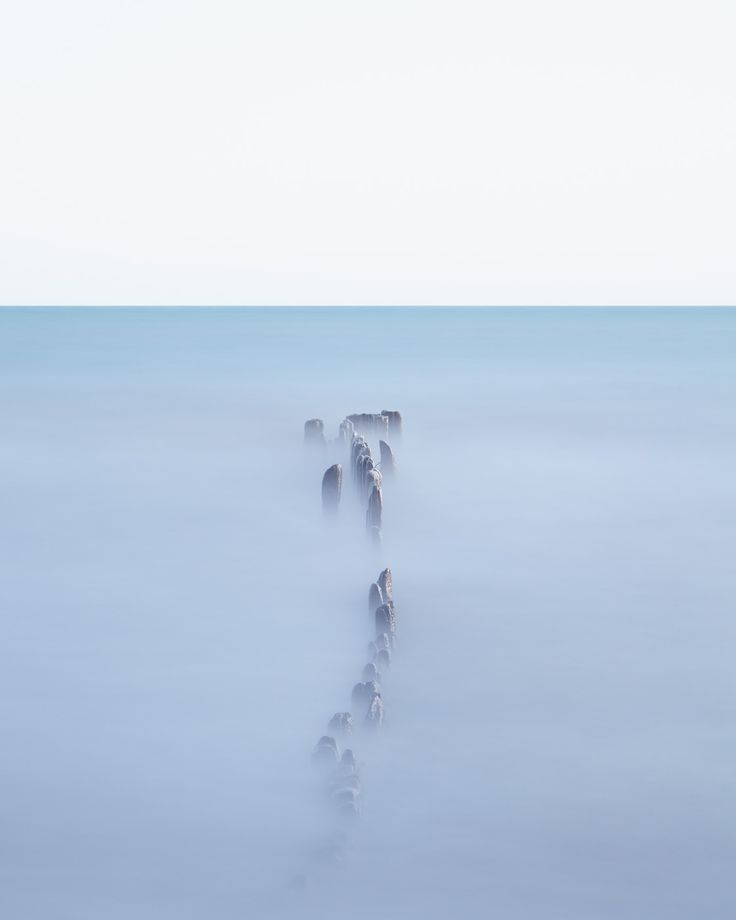 Nautical wall art featuring old wooden posts punctuating foggy water for a stunning, modern minimal piece of statement art. Let your mind wander.