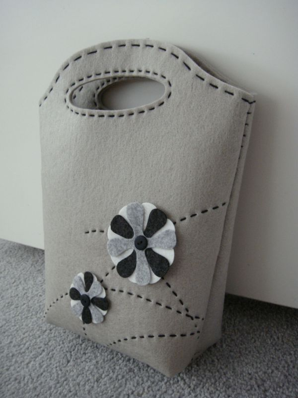 This kit is perfect for novice bag makers like me. It came with pre-cut, pre-punched materials and instructions. It's a simple grey felt bag with monochrome flowers. >Aligning the holes and st...