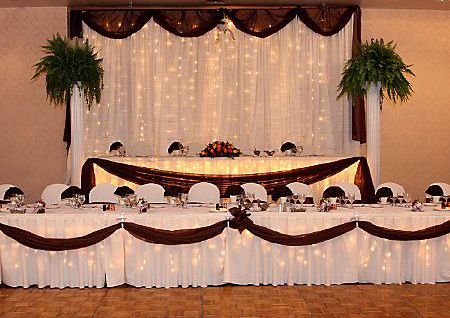 Swags can add your wedding colors to the head table.  To add more sparkle, hang mini lights behind the head table skirting and drape backdrop.    http://www.camelotspecialevents.com/Linen-Rental.htm