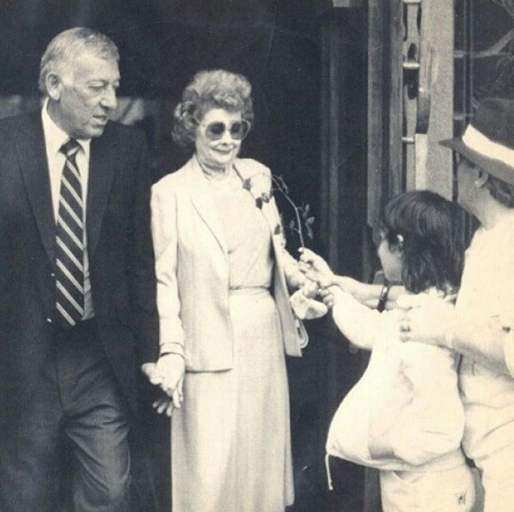 A little girl giving a flower to Lucy as she leaves the funeral of Desi Arnaz with her husband Gary Morton