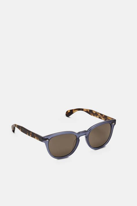 With the Sheldrake Plus, Oliver Peoples enlarges and enhances an Andy Warhol-inspired original. These bold sunglasses are framed by indigo and tortoiseshell acetate, both with a semi-matte finish. The pairing of cool and warm tones is balanced by carbon grey lenses made of mineral glass, which offers improved color definition and contrast as well as 100% UVA/UVB protection. Hand-laid functional plaques offer double adherence between the frame and hinge, ensuring strength and durability.