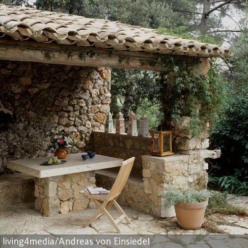Die Sitzecke aus Naturstein ist in einem schönen mediterranen Stil gebaut worden. Das Dach schützt vor Regen und Sonne. Dezente Deko rundet das Gesamtbild ab und …