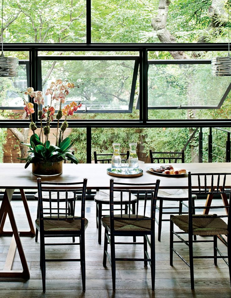 Designer Tia Cibani's home interiors are situated and decorated in a way that makes the most of the view of the garden beyond.The kitchen, dining room table is by Jonathan Adler. The rustic French chairs were found at an antiques dealer in Hudson.