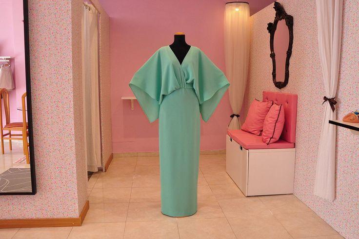 Vestido largo, cuya parte superior, con escote cruzado en la parte delantera, se prolonga con una capa que cubre la espalda y los brazos.