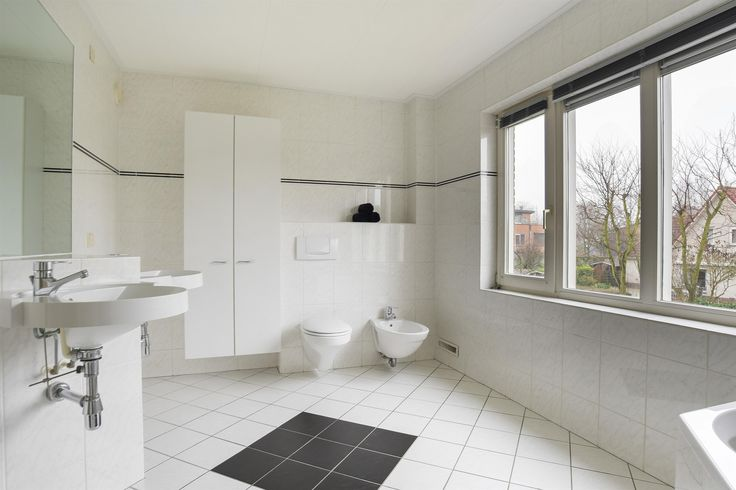 Deze moderne badkamer is geheel betegeld en voorzien van alle comfort. Zo zijn er twee wastafels, een toilet, bidet, douchecabine en een ligbad.