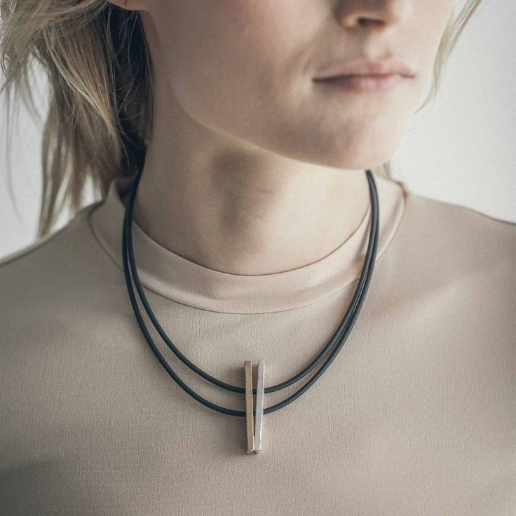 Dia - 2017 A mixture of textures and materials unite. Dia embodies harmony, made from a pair of reflecting hand-shaped bronze and pewter bars, strung on PVC strands imported from Germany.