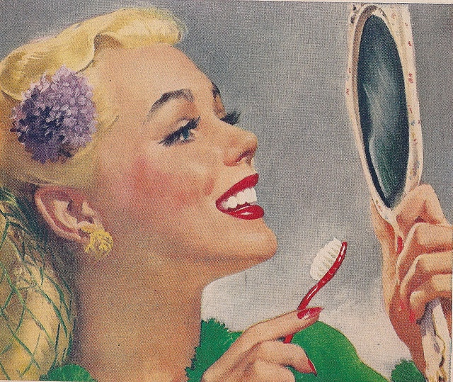 A cheerful, lovely woman admires her pearly whites, while sporting a lovely green snood and matching dress, in this 1946 Dr. West Toothbrush ad.