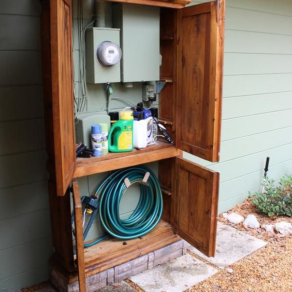 For a mere $10, this yard-sale armoire enabled handy homeowner Melodye Farrar to conceal her home's electric and cable boxes and create built-in storage for a garden hose and cleaning supplies.