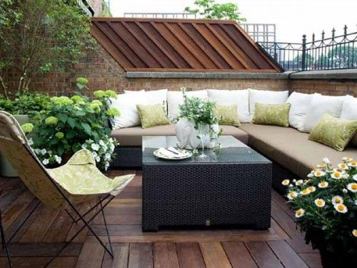 Basket roof terrace with sofa and wooden floor of planted chillout area