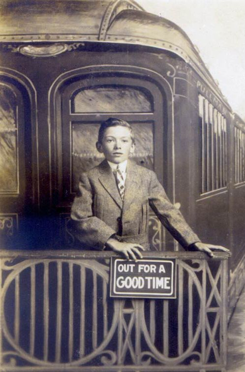 POSE:  Out for a Good Time. Well-dressed middle class lad in front of a train car prop. c. 1900. Clever way to hold a pose, too.