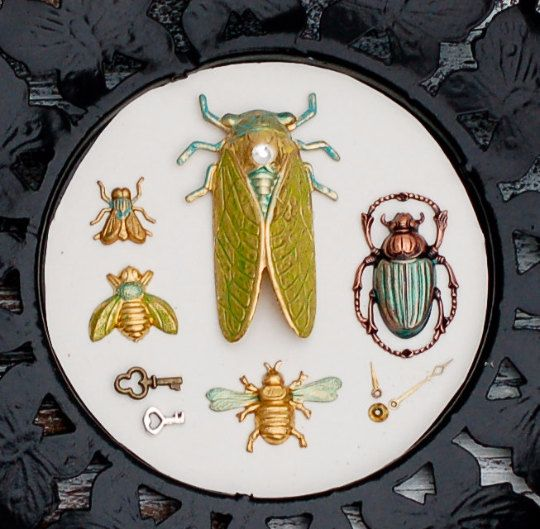 This cabinet of curiosity specimen piece is made up of hand painted brass insect stampings. A green cicada, beetle and bees are mounted on a white background with bits of watch parts, gears and tiny doll size skeleton keys. $35