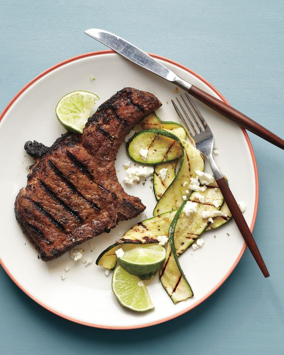 Ground coriander and cumin give these bone-in loin chops lots of spice flavor. Flame-kissed zucchini brightened with lime zest and feta is the…